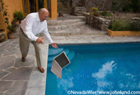 Picture of a older gentleman accidently dropping his laptop computer into a swimming pool. The mature man is bald with patches of gray hair on the sides and he is wearing glasses.  The senior is dressed in slacks and a white shirt.